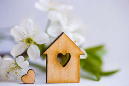 Wooden house with hole in form of heart surrounded by white flowering apricot branches on light background. Spring composition.