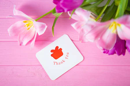 Greeting card with inscription Thank you and tender bouquet of beautiful pink tulips on pink wooden background. Spring gift.