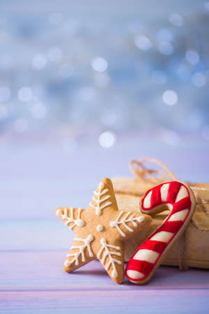 Foto de Glazed festive Christmas cookie in form of star and caramel cane on light bokeh background. Holiday bakery. New Year sweet gift. - Imagen libre de derechos