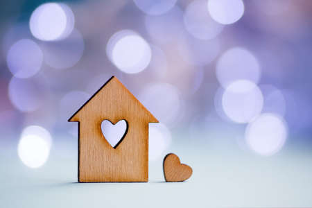 Photo pour Wooden icon of house with hole in the form of heart with little heart on pastel blurred background with light bokeh. Romantic card with copy space. Concept of sweet home. - image libre de droit