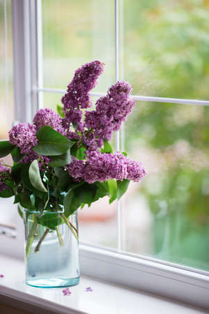 Spring tender bouquet of beautiful lilac in glass vase near window in daylight. Blooming flowers indoor. Concept of Women or Mother day gift.