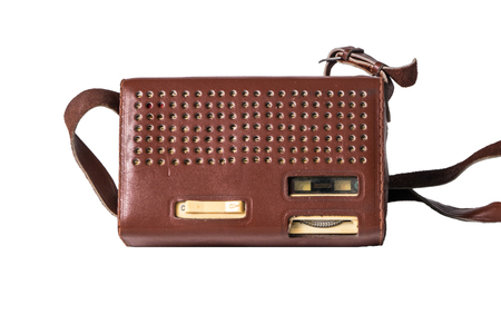 Old transistor radio in a leather case isolated on white