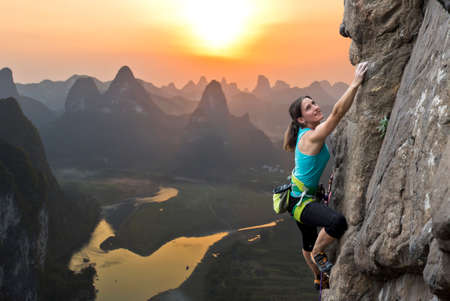 Female extreme climber conquers steep rock against the sunset over the river. China typical Chinese landscape with mountains and riverの写真素材
