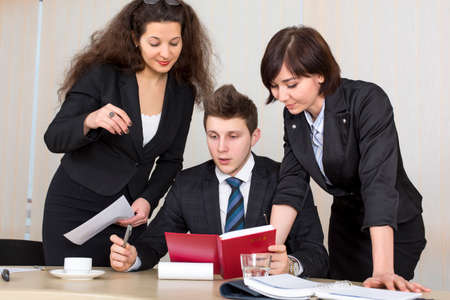 Group of business people discuss working schedule Three young businesspeople, one male and two females, are having discussion with diary, charts and other office supplies