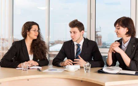 Hot discussion about financial impact of the project Multi ethnic business team have a discussion. Two nice females and one handsome male