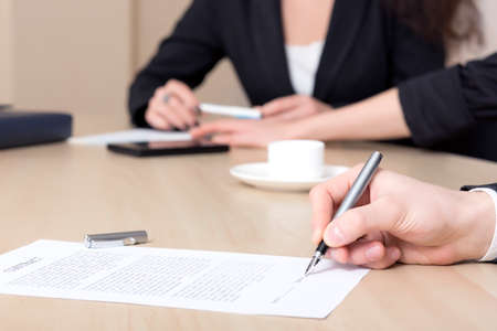 Photo pour Female businessperson signs contract Close up of female hand signing formal paper on the office table. The business counterpart on the background - image libre de droit