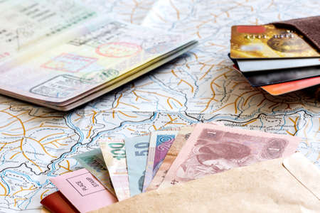 Photo for The composition of essential items for trip: passport with multiple entry stamps, cash notes from different countries, wallet and envelope, folded map of China, on wooden background - Royalty Free Image