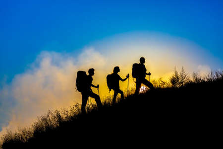 Foto de Silhouettes of three people walking with backpacks and other hiking gear up toward top wild grass mountain mother father daughter bright luminous sunrise sky background - Imagen libre de derechos