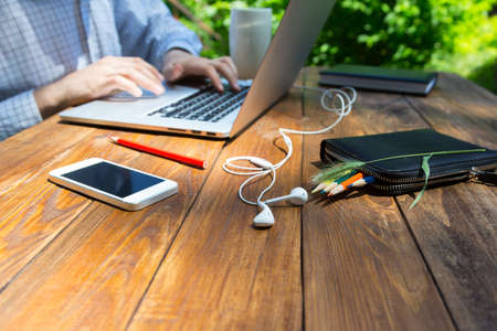 Photo for Boarded handmade wooden desk with smart phone headphones pencils and grass piece male body hard working on his electronic mail on laptop - Royalty Free Image