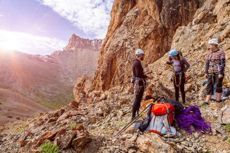 Photo pour Three people male female placing gear packing backpacks staying on rocky terrain at beginning of Climbing Route on Mountains blue Sky and Sun Rising Background - image libre de droit