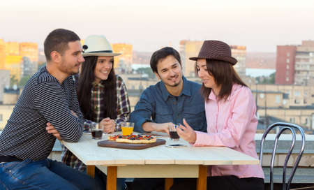 Young People Appointment at Outdoor Roof Top Cafe Table with Pizza and Drinks on Wood Desk and Evening Urban Background Multi-Ethnic Compa