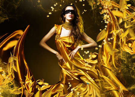 sensual adult woman in golden fabric and mask with leaves