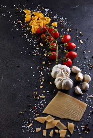Photo for Ingredients for cooking pasta on a black background. Pasta, sherry tomatoes, garlic, cheese, pepper and salt. - Royalty Free Image