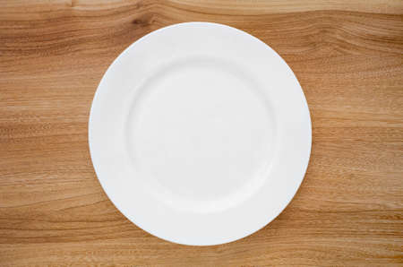 Photo pour Round white plate on a wooden table. View from above - image libre de droit
