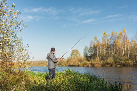 Photo pour Man stands on the shore with a fishing rod. On a sunny day. Beautiful fishing landscape - image libre de droit