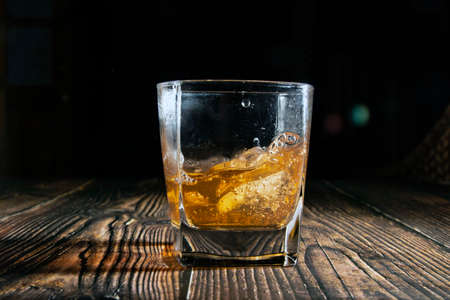 Photo pour Whiskey with ice cubes on a wooden table. An old tabletop with light and a glass of strong drink. A splash of whiskey in a glass while serving ice. - image libre de droit