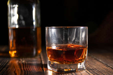 Photo pour Glass of whiskey with ice cubes, a bottle on a wooden table. An old tabletop with light and a glass of strong drink. - image libre de droit