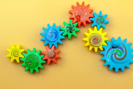 Photo pour Colored plastic gears on an orange background, top view. Communication and teamwork concept. - image libre de droit
