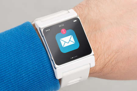 Photo pour Close up white smart watch with unread message icon on the screen is on hand - image libre de droit