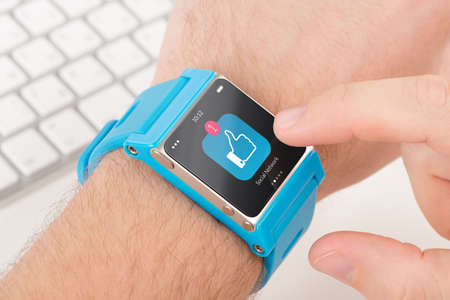 Male finger taps like icon on blue smart watch