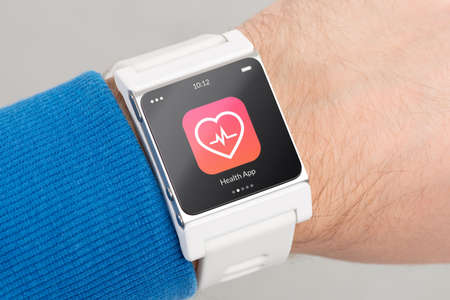 Photo pour Close up white smart watch with health app icon on the screen is on hand - image libre de droit