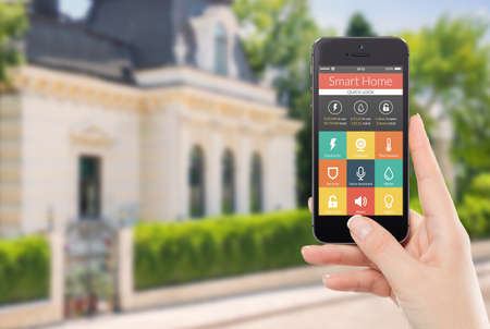Female hand holding black mobile smart phone with smart home application on the screen  Blurred house on the background  For access to all of the controls of your house and caring of home security