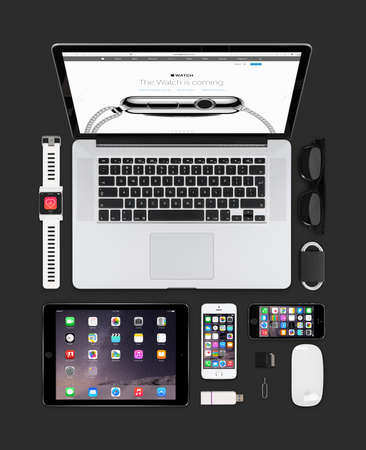 Varna, Bulgaria - February 09, 2015: Top view of Apple gadgets technology mockup consisting macbook pro with apple watch web page on the screen, ipad air 2, smart watch concept, iphone 5s, magic mouse.