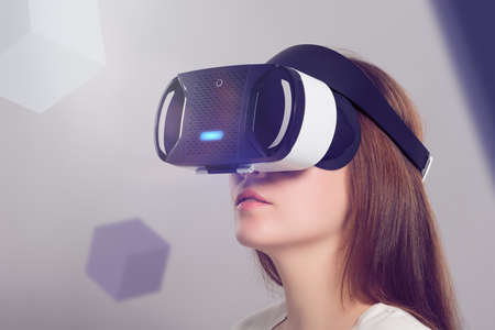 Photo pour Woman in VR headset looking up at the objects in virtual reality. VR is a computer technology that simulates a physical presence and allows the user to interact with environment. - image libre de droit