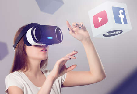Photo pour Varna, Bulgaria - March 10, 2016: Woman in VR headset looking up and interacting with Facebook Youtube Steam VR content. Facebook Google & Steam believes that VR is the future of content consumption. - image libre de droit