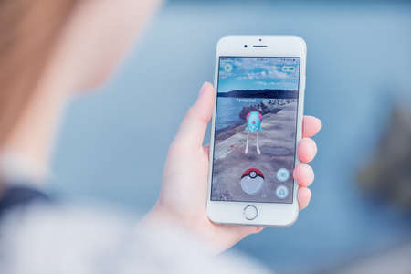 Photo pour Varna, Bulgaria - Jul 19, 2016: Nintendo Pokemon Go augmented reality mobile application game with Tentacool pokemon catching on Apple iPhone 6S in female hand. Blurred view on the background. - image libre de droit