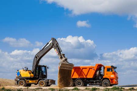 Photo pour A yellow backhoe loader loads the earth into a truck - image libre de droit