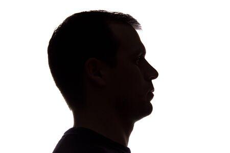 Photo pour Portrait of a young man, unshaven, side view - dark isolated silhouette - image libre de droit