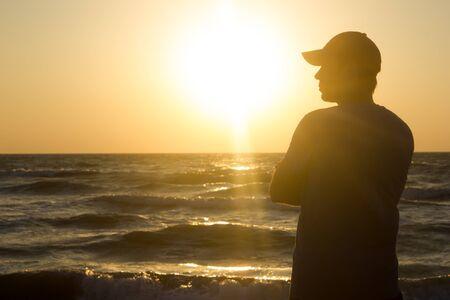 Photo pour Portrait of a young man in cap on the beach - at sunrise - image libre de droit