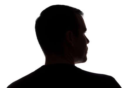Photo pour Portrait of a young man, unshaven, back view - dark isolated silhouette - image libre de droit