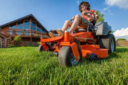 A man is mowing backyard on a riding zero turn lawnmower