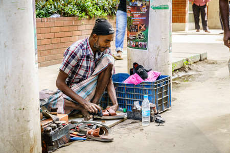 Photo pour Chittagong, Bangladesh, December 22, 2017: shoe repair service on a street of Chittagong in Bangladesh - image libre de droit