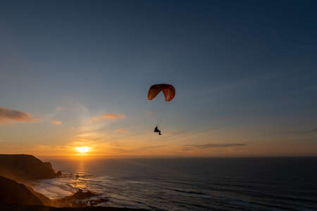Photo for Paraglider flying over thesea shore at sunset. Paragliding sport concept. - Royalty Free Image