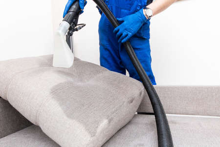 Photo pour Cleaning service. Man janitor in gloves and uniform vacuum clean sofa with professional equipment. - image libre de droit