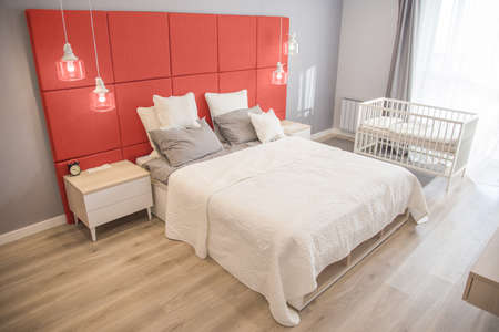 Foto de Interior of the room in light colors. Bedroom with a bed and a cot in colors of the year 2019 Living coral - Imagen libre de derechos