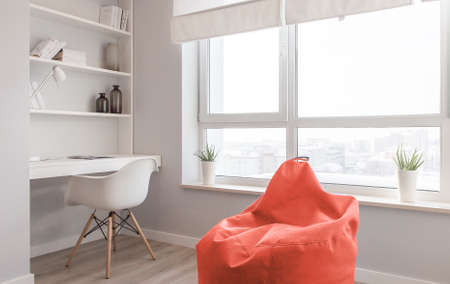 Foto de Interior of the apartment. Design of the room in Scandinavian style, workplace near the window in colors of the year 2019, living coral. - Imagen libre de derechos