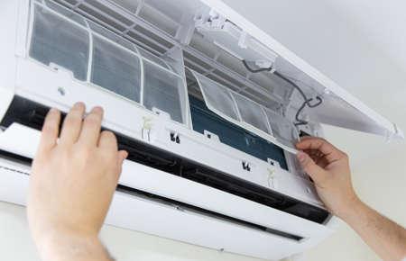 Photo pour Male technician cleaning air conditioner indoors. - image libre de droit
