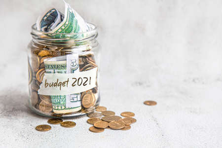 Photo pour Budget 2021. Glass jar with money, coins and notes, savings, loans and mortgages. - image libre de droit