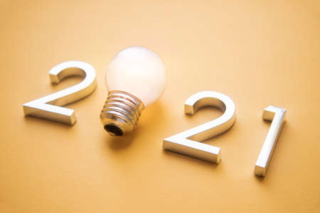 Photo for metal numbers 2021 with a burning light bulb. New ideas in the new year - Royalty Free Image