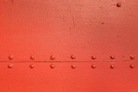 Photo pour Red vintage industrial texture with symmetrical horizontal metal rivets - image libre de droit