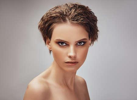 Photo pour Portrait of a charming girl with bare shoulders, on a gray background. Beautiful woman charm makeup model - image libre de droit