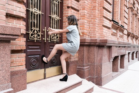 Photo pour Young woman in short gray dress and shoes with heels pulling the handle of vintage door leaning into her leg - image libre de droit
