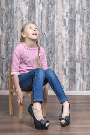 Foto de young girl sitting on a wooden chair looks frustrated up trying on her mother's high-heeled shoes - Imagen libre de derechos