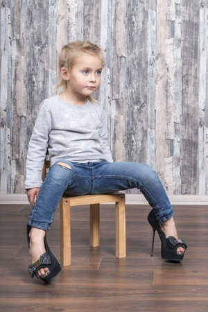 baby girl sitting on a wooden chair, legs wearing her mother big shoes