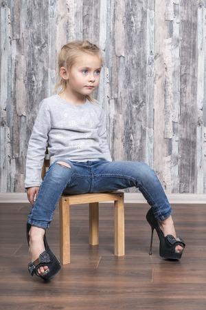 Foto de baby girl sitting on a wooden chair, legs wearing her mother big shoes - Imagen libre de derechos