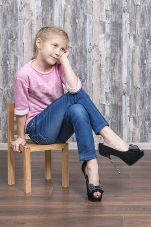 Photo for Young beautiful girl in her mother shoes sits on a small wooden chair and dreams of leaning on her arm - Royalty Free Image